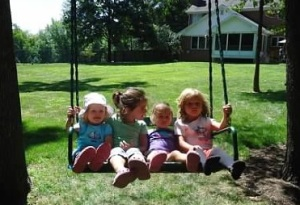 MOMS Club of Uniontown Ohio picture, 4 small children sitting together on a swing outside enjoying the day.