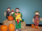 MOMS Club of Uniontown Ohio picture, child wearing Halloween costume standing in front of scarecrow, pumpkin, and straw bale decorated Thanksgiving scene.